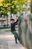 El niño mira a través del agujero en la cerca Imagen de archivo