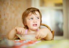 El niño mismo come de la placa Imagen de archivo