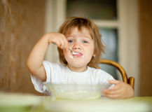 El niño mismo come de la placa con la cuchara Imagenes de archivo