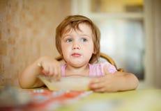 El niño mismo come de la placa con la cuchara Fotos de archivo
