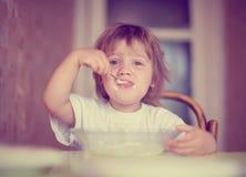El niño mismo come de la placa con la cuchara Imágenes de archivo libres de regalías