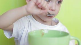 El niño mismo come la comida con una cuchara de una placa, sentándose en una tabla Primer almacen de metraje de vídeo
