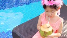 El niño, muchacha, bebe el agua del coco en la piscina metrajes