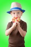El niño muestra el pulgar con el caramelo Foto de archivo libre de regalías