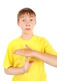 El niño muestra que el tiempo hacia fuera gesticula imagen de archivo