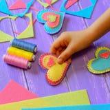 El niño muestra un ornamento del corazón del fieltro El niño hizo un corazón del fieltro para el día de tarjetas del día de San V Imágenes de archivo libres de regalías