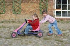 El niño mueve el coche del pedal Fotos de archivo