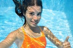 El niño nada en adolescente activo subacuático, feliz de la piscina que se zambulle la muchacha y se divierte bajo el agua, la ap Imagen de archivo