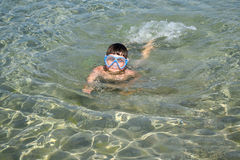 El niño nada en máscara del equipo de submarinismo en el mar fotos de archivo