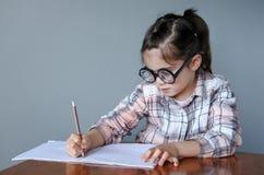 El niño Nerdy escribe una historia Imagen de archivo libre de regalías