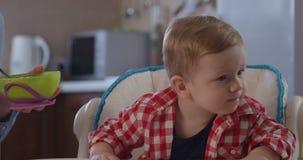 El niño no quiere comer la comida y a la madre que intentan alimentar al bebé almacen de metraje de vídeo