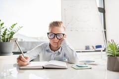 El niño pensativo está actuando como hombre de negocios Foto de archivo