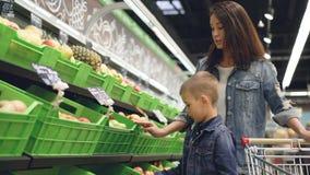 El niño pequeño adorable está eligiendo manzanas en el departamento de la fruta y verdura en colmado, su madre atractiva es almacen de metraje de vídeo