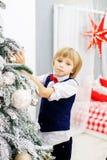 El niño pequeño adorna un árbol de navidad en el cuarto Winte del concepto Foto de archivo libre de regalías