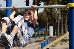 El niño pequeño alcanza en la barra horizontal Imagen de archivo libre de regalías