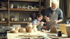 El niño pequeño alegre está lanzando pedazos de arcilla en la tabla de trabajo mientras que ayuda a su abuelo en taller del ` s d almacen de metraje de vídeo