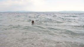 El niño pequeño alegre está nadando en el mar adriático Ondas en el mar Croacia almacen de video