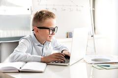El niño pequeño alegre está trabajando en oficina Imagenes de archivo