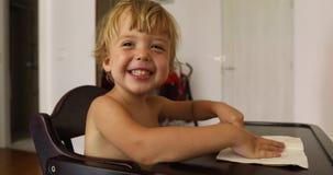 El niño pequeño alegre se sienta en la silla y las risas del niño almacen de video