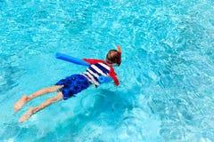 El niño pequeño aprende nadar solamente con los tallarines de la piscina imágenes de archivo libres de regalías