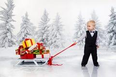 El niño pequeño arrastra un montón enorme de los regalos de la Navidad foto de archivo