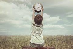 El niño pequeño aumenta en el cielo un reloj en un paisaje surrealista Foto de archivo