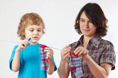 El niño pequeño ayuda a su madre a colgar para arriba sus calcetines Imagen de archivo