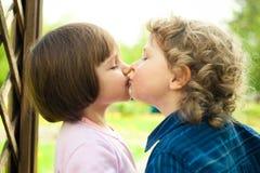 El niño pequeño besa a la muchacha Fotos de archivo