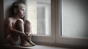El niño pequeño cambiante que se sienta en las gotas de agua de observación del alféizar va abajo de los windowglass almacen de metraje de vídeo