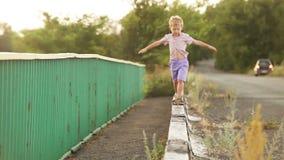 El niño pequeño camina en el encintado del camino almacen de video