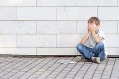 El niño pequeño cansó triste y subrayado con PC de la tableta Embrome sentarse en la tierra, llevando a cabo su cabeza, los ojos  Fotografía de archivo