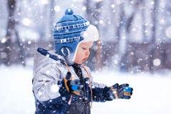 El niño pequeño coge los copos de nieve por la tarde escarchada del invierno Foto de archivo libre de regalías