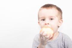 El muchacho come la manzana Imagen de archivo