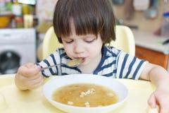 El niño pequeño come la sopa de guisantes con panes cocidos Foto de archivo