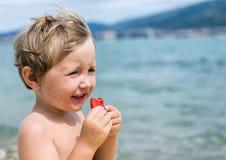 El niño pequeño come las fresas con placer Imagenes de archivo