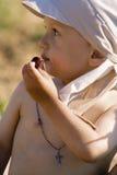 El niño pequeño come una cereza madura Imagen de archivo