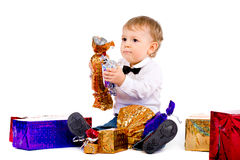 El niño pequeño con el dulce y los regalos grandes Imagen de archivo libre de regalías