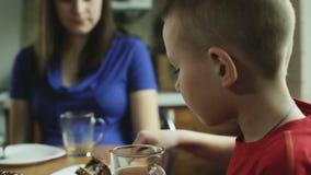 El niño pequeño con el pelo corto está comiendo la torta y el té de consumición almacen de metraje de vídeo
