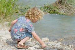 El niño pequeño con el pelo rubio juega la orilla del agua imagen de archivo libre de regalías