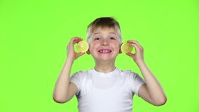 El niño pequeño con las rebanadas de limón las lame y muestra muecas Pantalla verde Cámara lenta metrajes