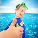 El niño pequeño con los pulgares sube gesto en el mar Fotos de archivo