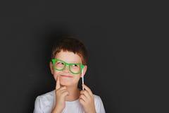 El niño pequeño con los vidrios verdes acerca a la pizarra Imagenes de archivo