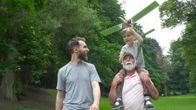 El niño pequeño con el modelo del aeroplano y el aumento del abuelo entrega el parque verde en fondo que disfruta de vida y de la almacen de metraje de vídeo