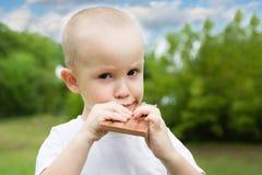 El niño pequeño con placer come es chocolate Imagenes de archivo