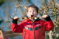 El niño pequeño con placer come vehículos asados a la parilla Imagen de archivo libre de regalías