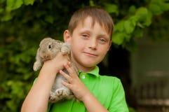 El niño pequeño con un conejo en las manos Imagen de archivo libre de regalías