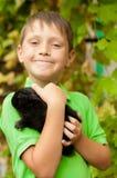 El niño pequeño con un conejo en las manos Imagen de archivo