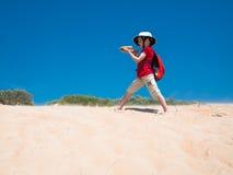 El niño pequeño con una mochila y una ballesta en sus manos se coloca en las arenas de oro y las tomas apuntan Fotos de archivo