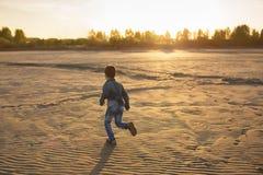 El niño pequeño corre en una playa en la puesta del sol Foto de archivo