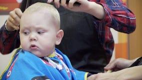 El niño pequeño corta al peluquero Él se sienta en una silla que parezca un coche Mamá que distrae y que juega con él Primer prin almacen de video